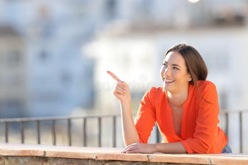 Turista feliz que señala en el lado en un balcón fotografía de archivo libre de regalías