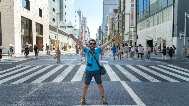 Turista feliz y emocionado en el distrito que hace compras Ginza con la calle famosa de Chuo Dori, Tokio, Japón fotos de archivo