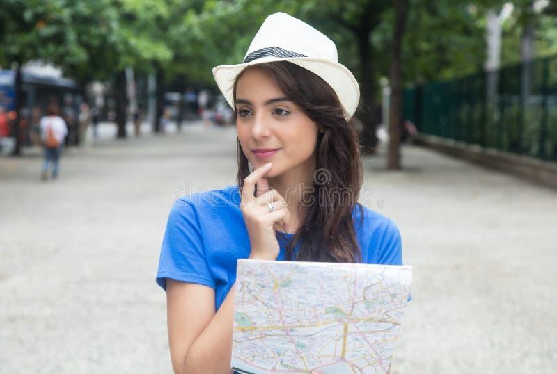 Turista femenino caucásico joven con el mapa que mira alrededor foto de archivo libre de regalías