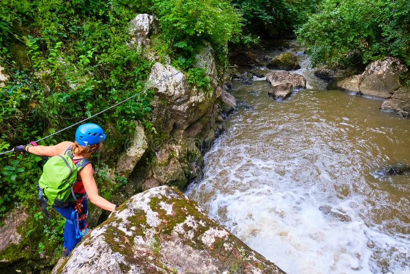 Turista femenino con vía el engranaje del ferrata que cruza una sección del cable sobre Paraul Racilor en la garganta de Tureni/C fotos de archivo