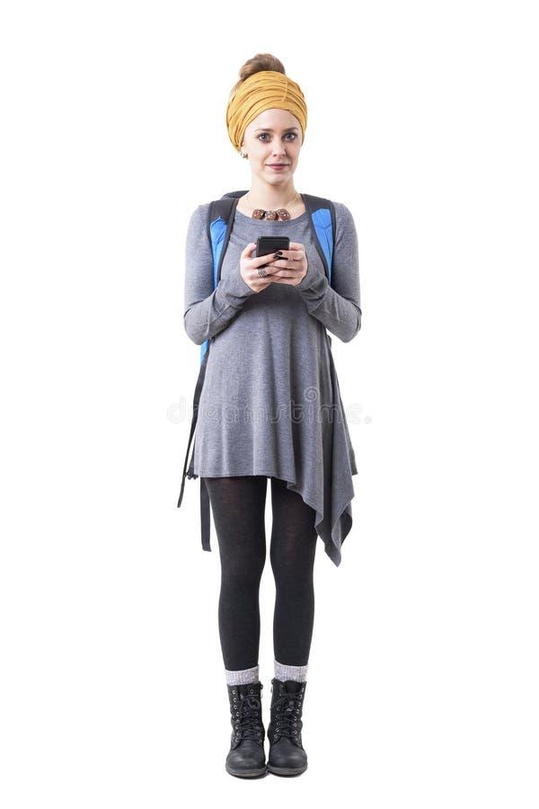 Turista femenino elegante joven con el turbante y la mochila usando el teléfono móvil que mira la cámara foto de archivo