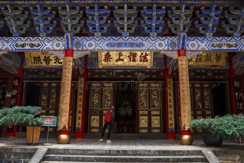 Turista femenino en templo budista chino tradicional en la ciudad de Kunming imagenes de archivo