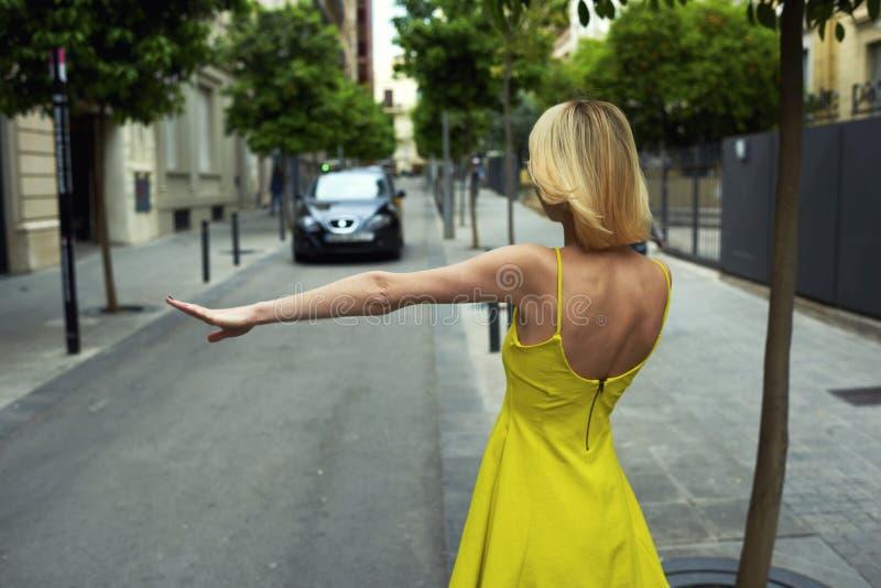 Turista femenino joven con el gesto de mano que para el taxi en el ambiente urbano imagenes de archivo