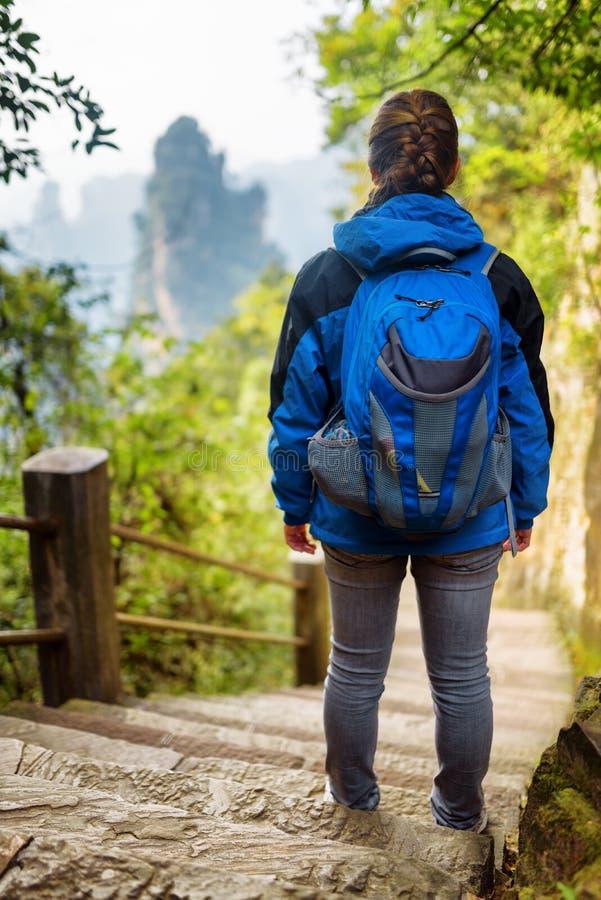 Turista femenino joven con la mochila azul que se coloca en las escaleras de piedra foto de archivo