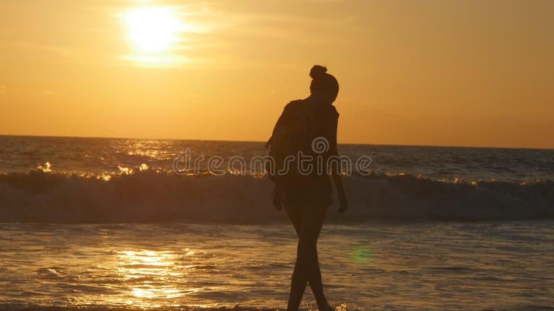 Turista femenino joven con la mochila que camina a lo largo de la playa del mar en la puesta del sol Mujer joven hermosa del viaj foto de archivo