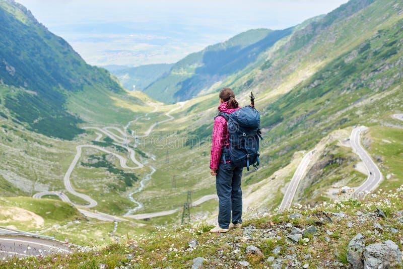 Turista femenino joven que mira abajo a enrollar el camino de Transfagarshan entre cuestas y montañas rocosas verdes en Rumania foto de archivo libre de regalías
