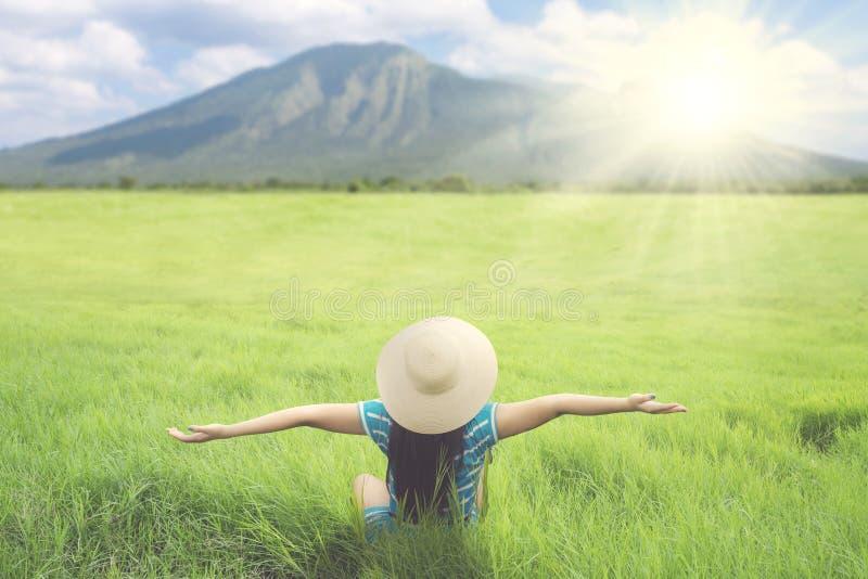 Turista femenino que estira sus manos en el prado imágenes de archivo libres de regalías