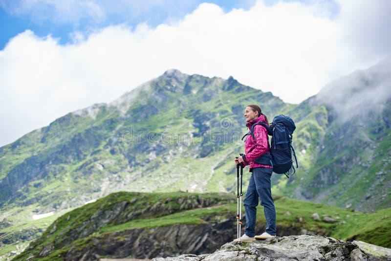 Turista femenino sonriente del positivo que admira la naturaleza magnífica con las montañas rocosas verdes de niebla en Rumania imagen de archivo