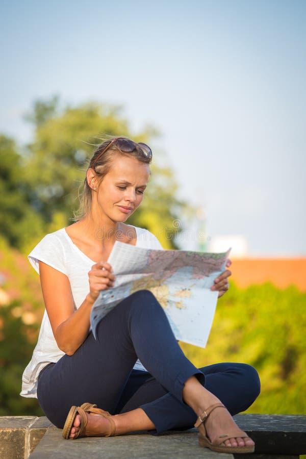 Turista femminile abbastanza giovane che studia una mappa immagini stock libere da diritti