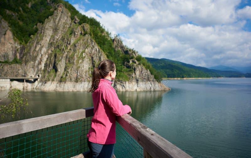 Turista femminile castana che esamina lontano le viste piene d'ammirazione di distanza delle montagne rocciose e del lago verdi immagini stock libere da diritti