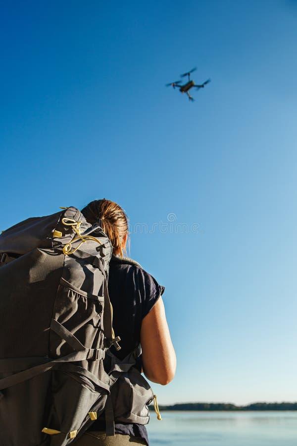 Turista femminile che controlla il fuco con il telecomando Posizione della riva del fiume immagine stock libera da diritti