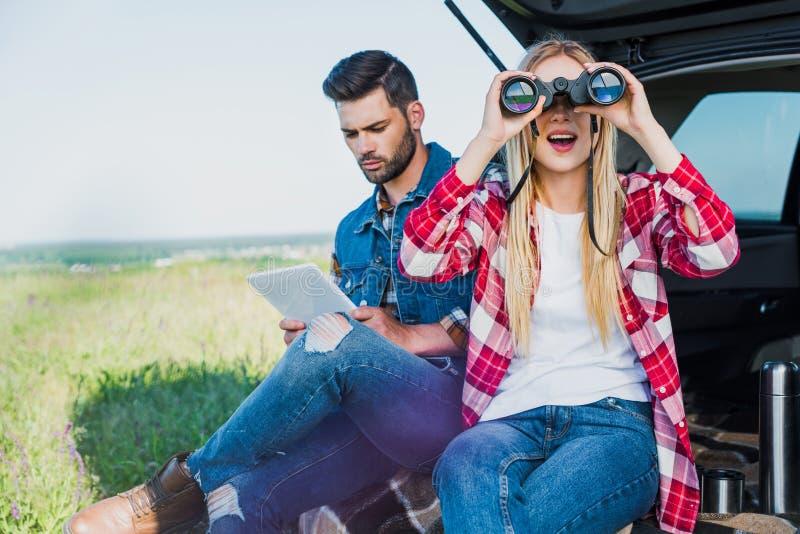 turista femminile che guarda tramite il binocolo mentre il suo ragazzo immagini stock libere da diritti