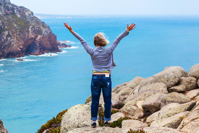 Turista femminile felice che sta sul capo Roca, Sintra, Portogallo immagine stock