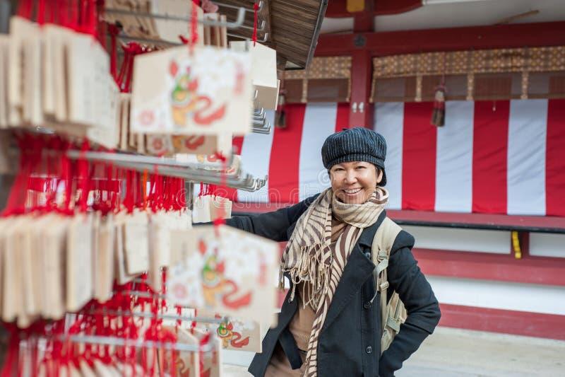 Turista femminile senior asiatico in costume di inverno immagine stock libera da diritti