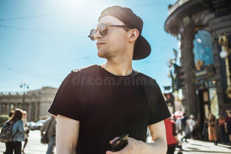 Turista hermoso del hombre con el teléfono Hombre joven que se coloca en una calle de la ciudad europea Navegación, concepto del  fotos de archivo libres de regalías