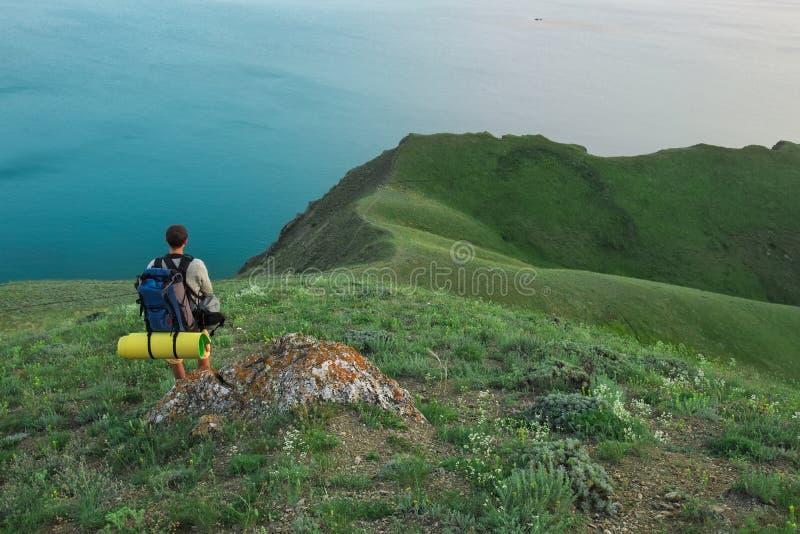 Turista joven encima de una montaña que goza del mar fotos de archivo