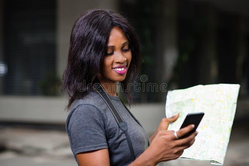 Turista joven que sostiene un mapa y que usa su teléfono móvil imagen de archivo libre de regalías