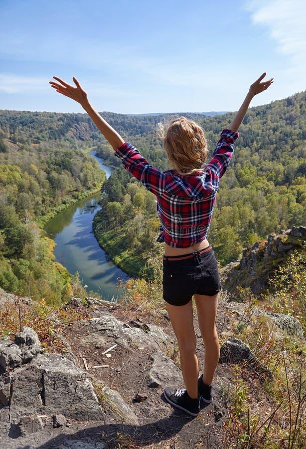 Turista louro novo da mulher em um penhasco sobre a BERD do rio imagens de stock royalty free