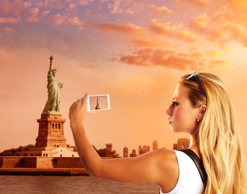 Turista louro que toma a foto à estátua da liberdade NYC fotografia de stock royalty free