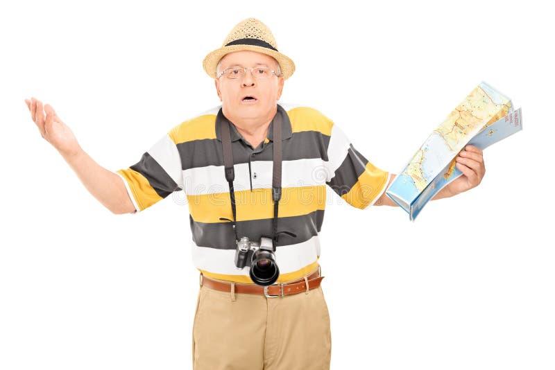 Turista maduro confuso que guarda um mapa fotos de stock royalty free