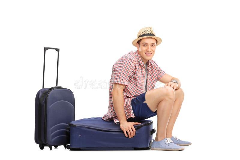 Turista masculino alegre que senta-se em sua bagagem imagens de stock