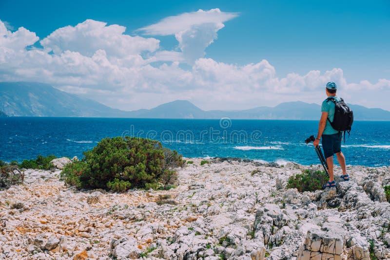 Turista masculino com câmera que admira o cenário excitante da nuvem sobre a cordilheira na costa de mar Mediterrâneo fotos de stock
