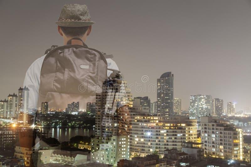 Turista masculino con el embalador trasero que coloca y que mira la ciudad, doble imagen de archivo libre de regalías