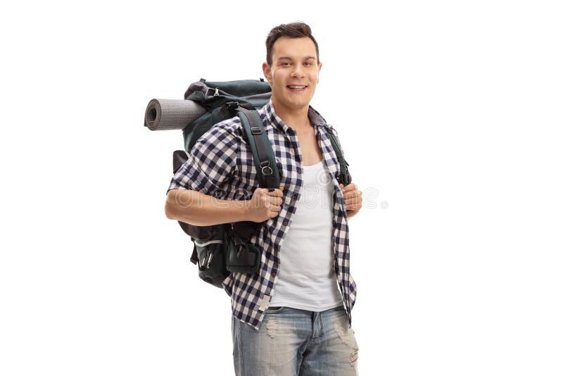 Turista masculino con una mochila que sonríe en la cámara foto de archivo