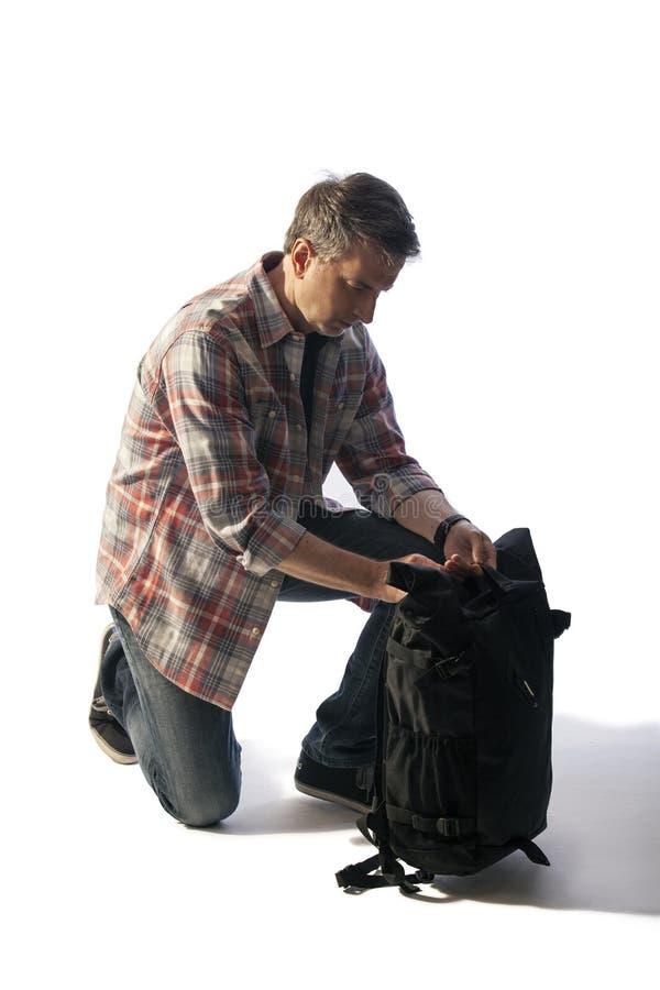 Turista masculino de mediana edad que embala un Lit de la mochila por puesta del sol fotografía de archivo