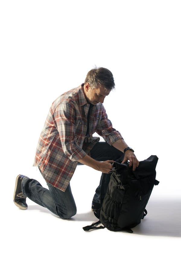 Turista masculino de mediana edad que embala un Lit de la mochila por puesta del sol imagen de archivo libre de regalías