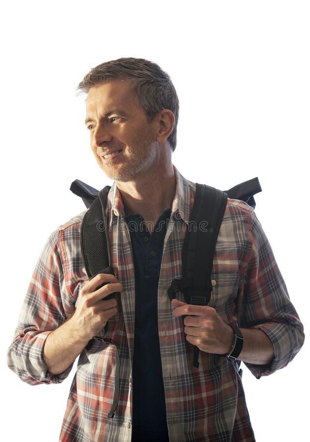 Turista masculino de meia idade com um Lit da trouxa pelo por do sol imagem de stock