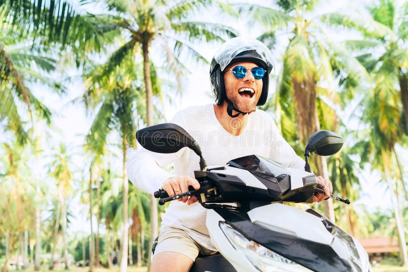 Turista masculino de sorriso e gritando feliz no capacete e óculos de sol que montam o 'trotinette' do velomotor durante suas fér foto de stock