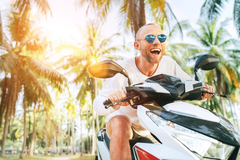 Turista masculino de sorriso feliz nos óculos de sol que montam o 'trotinette' do velomotor durante suas férias tropicais sob pal fotografia de stock