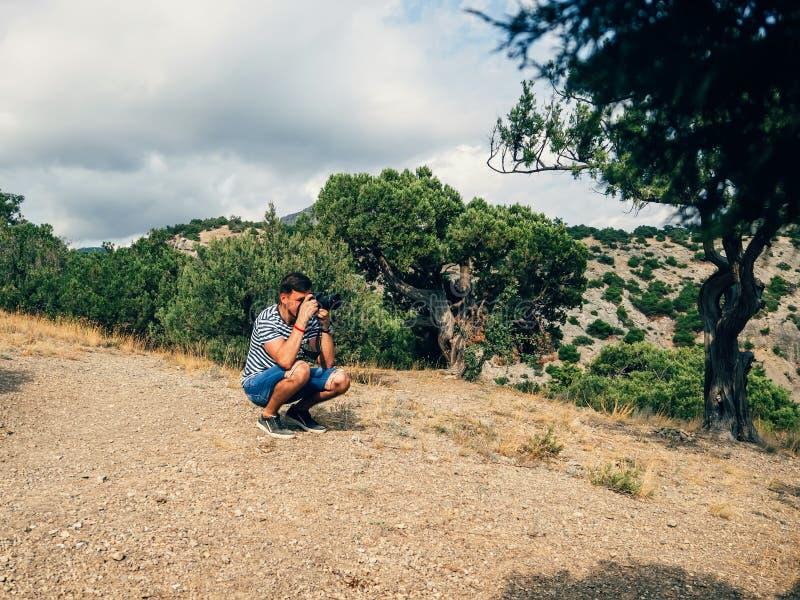 Turista masculino del fotógrafo que fotografía el paisaje en una cámara profesional fotografía de archivo