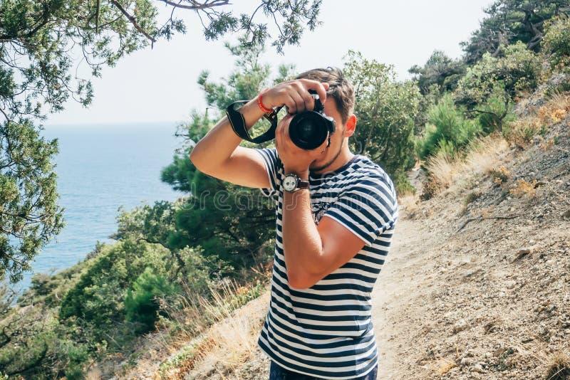 Turista masculino del fotógrafo que fotografía una cámara profesional fotos de archivo libres de regalías