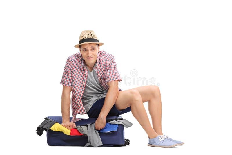 Turista masculino triste que senta-se sobre uma mala de viagem embalada imagens de stock royalty free