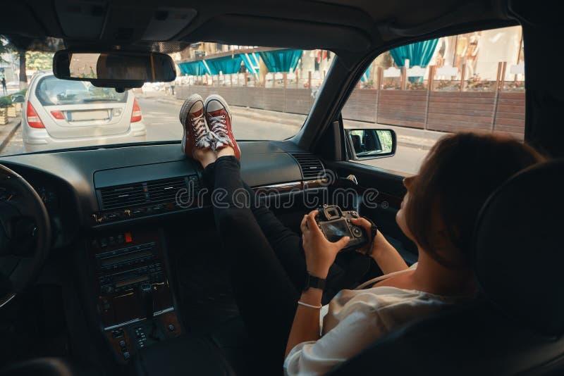 Turista moderno de la mujer, fotógrafo que se relaja en el coche que sostiene a imagen de archivo