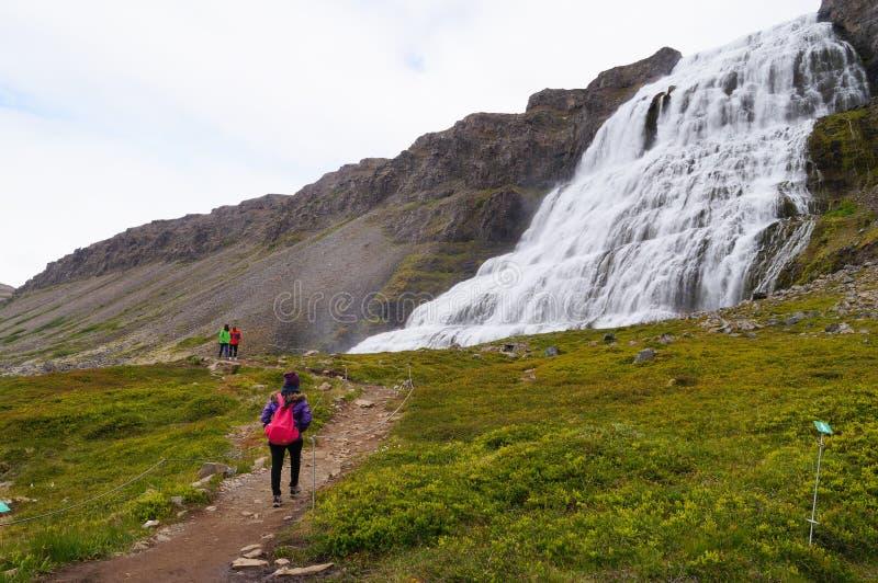 Turista não identificado que anda à cachoeira de Dynjandi, Islândia imagem de stock