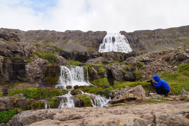 Turista não identificado que toma a imagem da cachoeira de Dynjandi, Islândia foto de stock royalty free