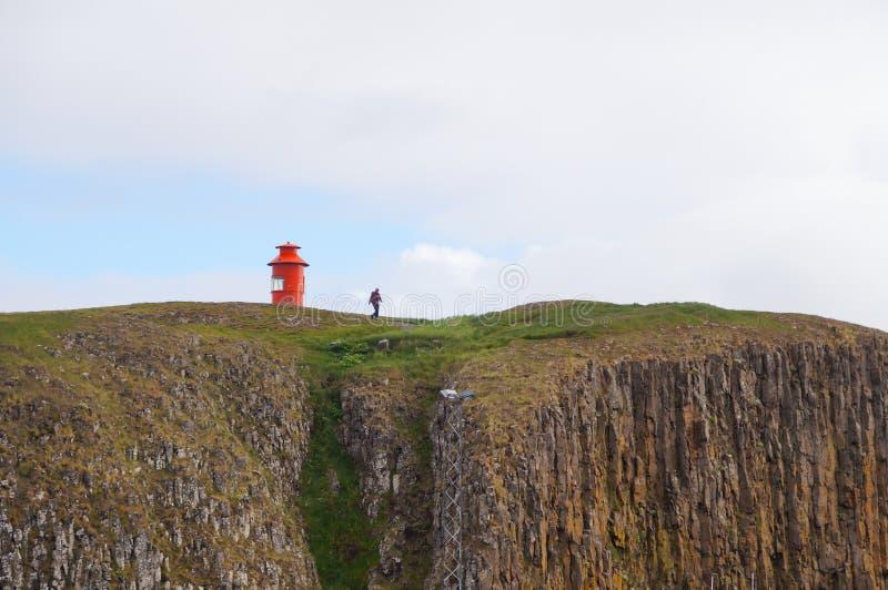 Turista non identificato che cammina giù dalla scogliera in Stykkisholmur, Islanda fotografie stock
