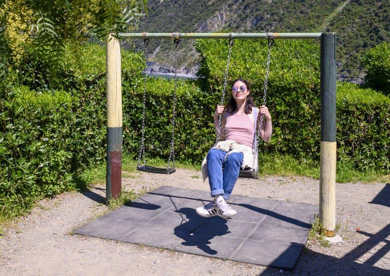 Turista norteamericana en columpio en Manarola, la segunda más pequeña de las famosas ciudades de Cinque Terre, Italia imágenes de archivo libres de regalías