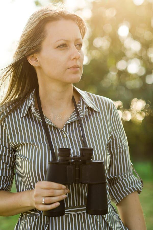 Turista novo atrativo com os binóculos exteriores na floresta - exterior imagens de stock