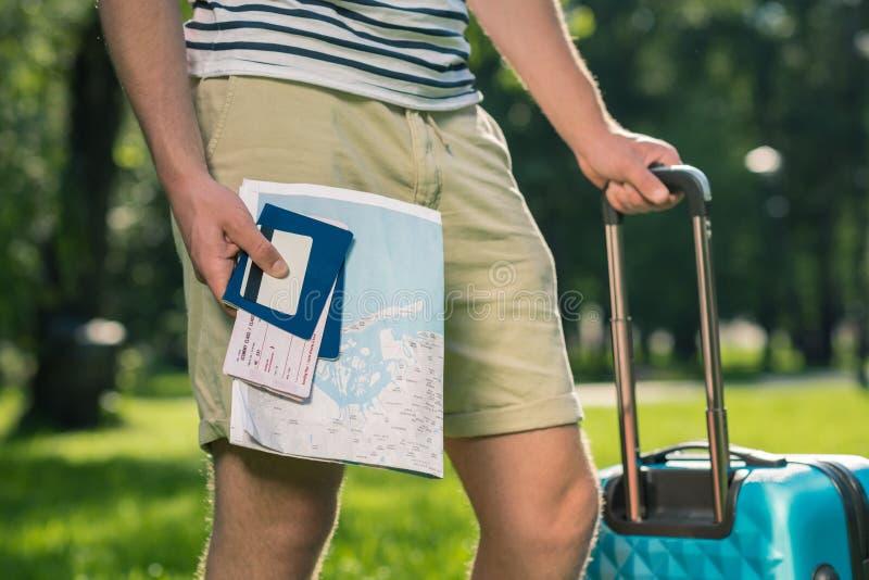 Turista novo com a mala de viagem que guarda o mapa, os passaportes, os bilhetes e o cartão de crédito no parque fotografia de stock