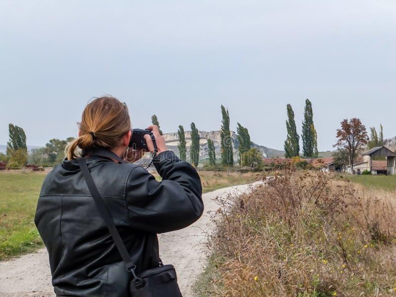 Turista novo em fotografias pretas do casaco de cabedal a paisagem crimeana imagem de stock