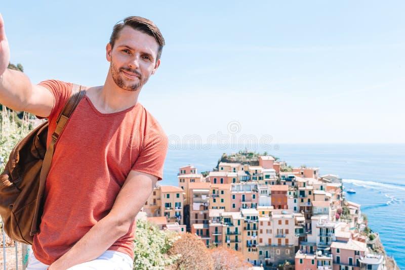 Turista novo nos ?culos de sol que tomam o selfie com vista c?nico de Manarola, Cinque Terre, Liguria, It?lia fotografia de stock