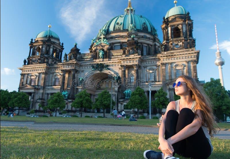 Turista pensativo de la muchacha que se sienta en Alemania cerca de la catedral de Berlín opinión de la catedral de Berlín en Ale foto de archivo libre de regalías