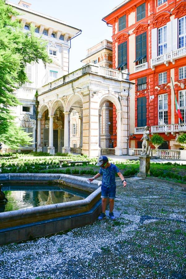 turista pequeno perto de Palazzo Rosso, Genoa, Itália foto de stock royalty free