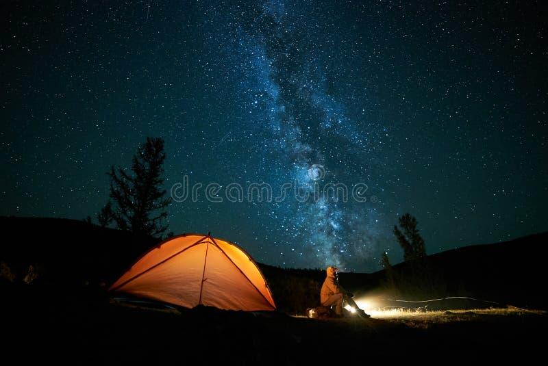 Turista perto de sua barraca do acampamento na noite fotografia de stock royalty free