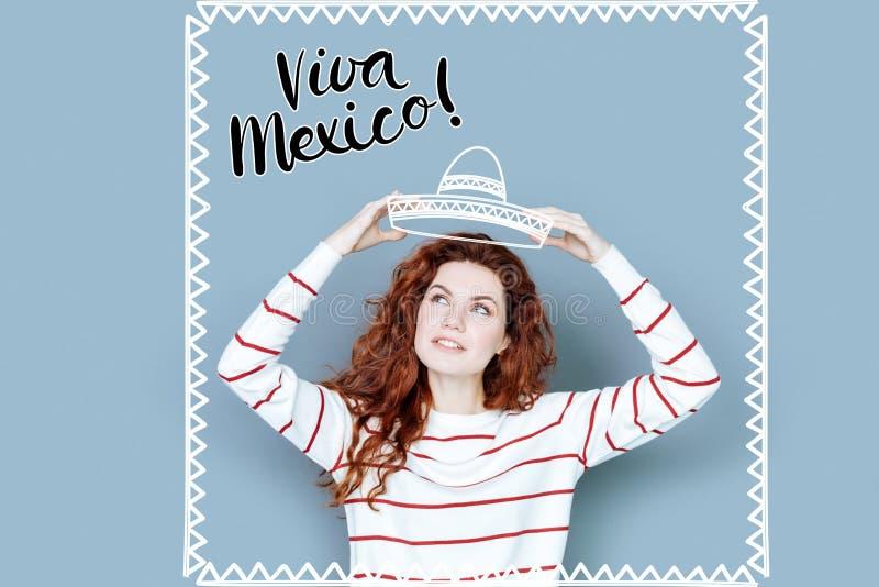 Turista positivo que lleva un sombrero mientras que estando en México imagen de archivo libre de regalías