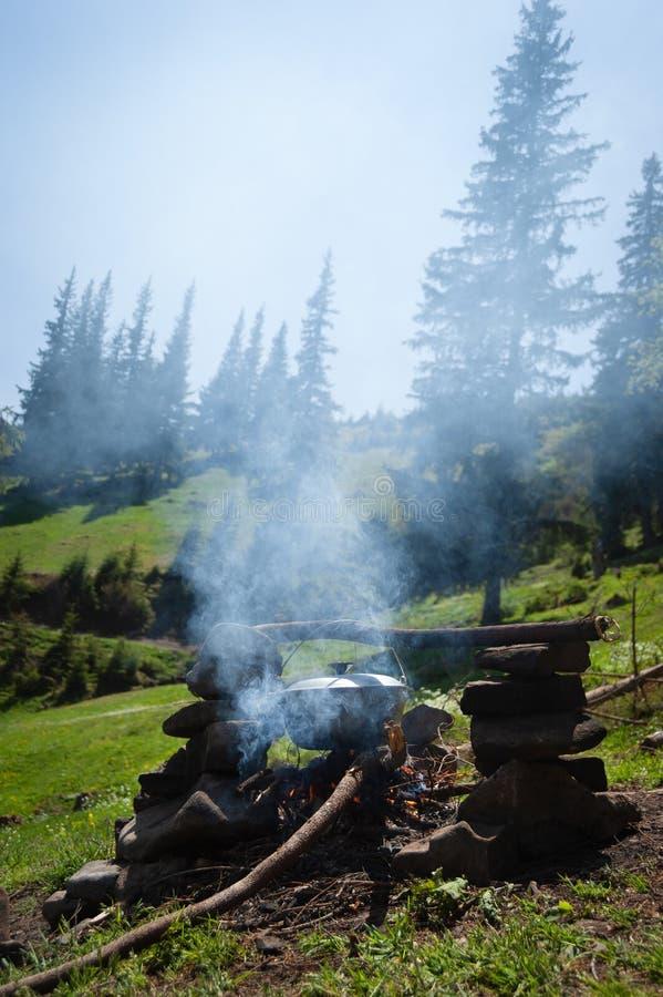 Turista que acampa con un fuego en las montañas imagenes de archivo
